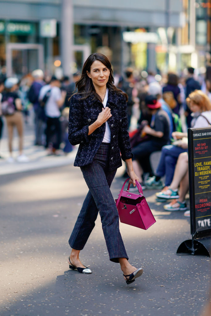 A guest wears a dark blue tweed jacket, a pink Hermes bag, flared pants, silver shoes, during London Fashion Week September 2018 on September 17, 2018 in London, England.